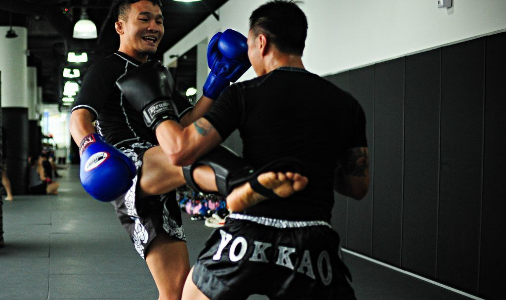 Multiple-time Muay Thai World Champion Petchboonchu FA Group teaches a student the fundamentals of sparring.